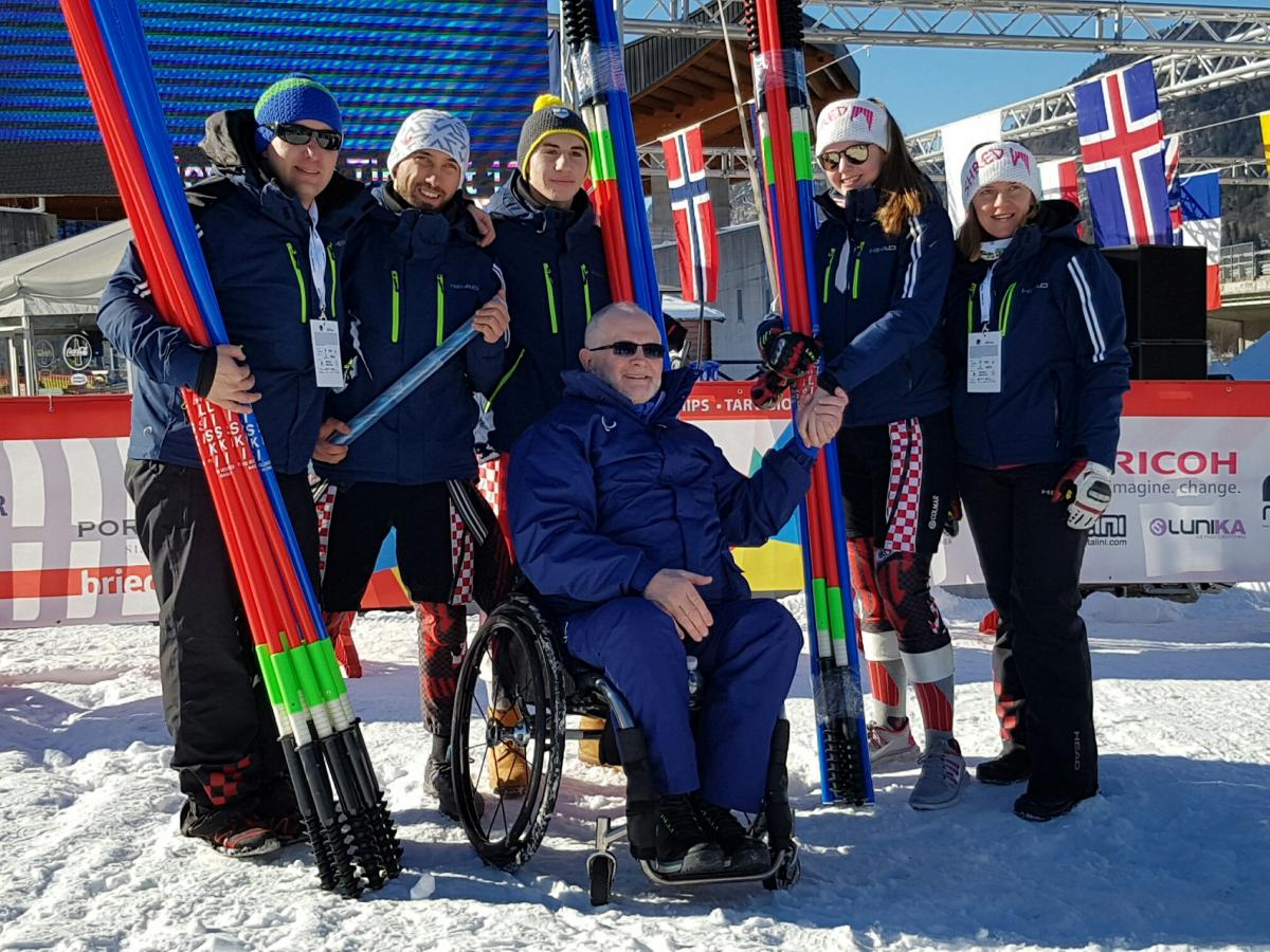Group picture with skiers and man in wheelchair