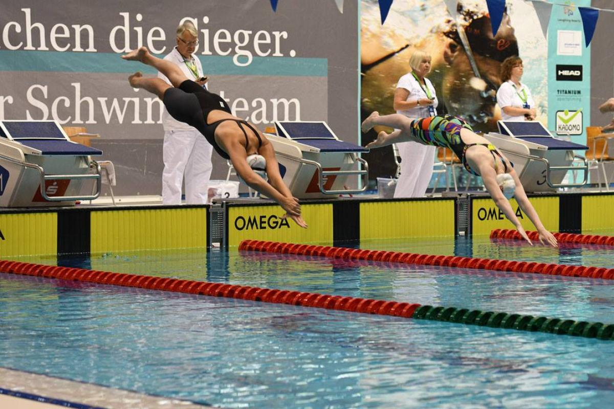 two female swimmers jump into the pool at the start of a race
