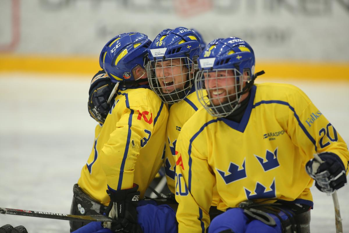 a group of Para ice hockey players hug on the ice