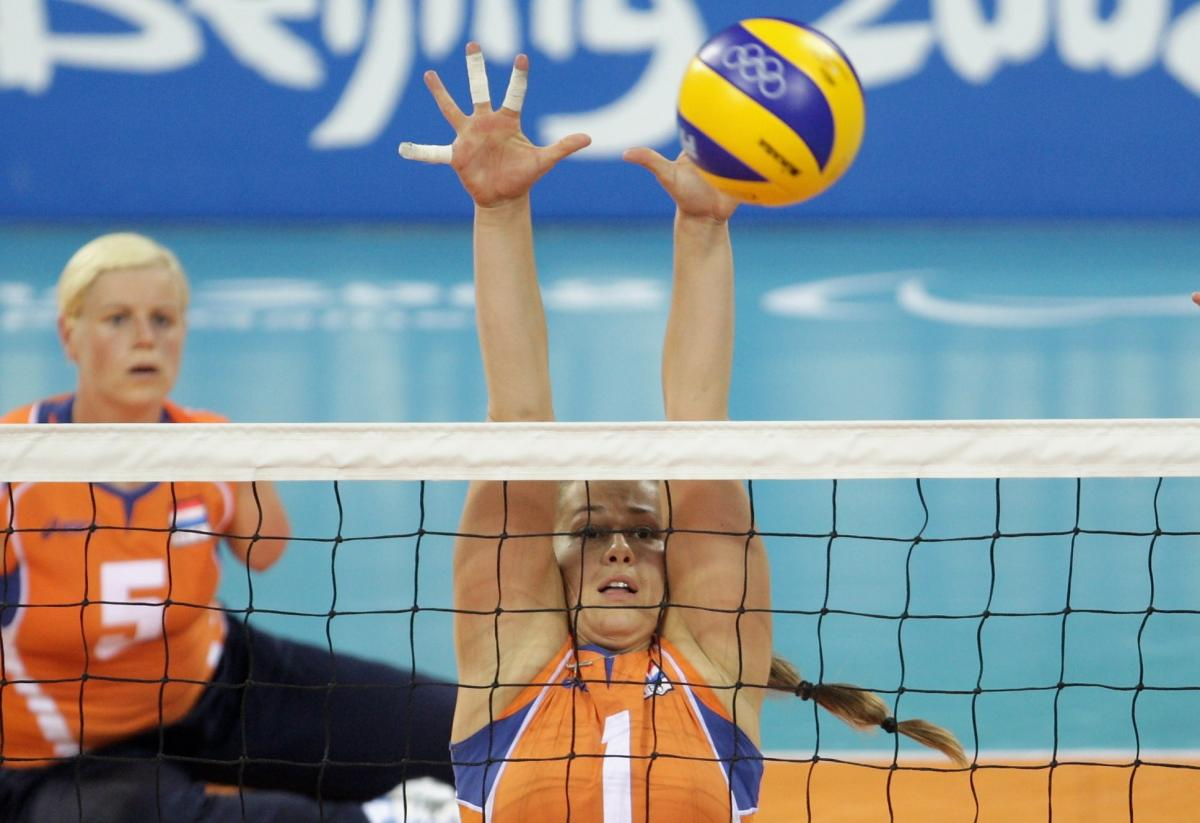 a female sitting volleyball player tries to block a spike