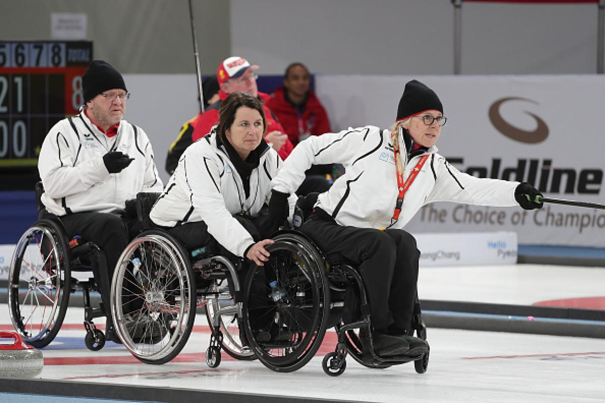 a female wheelchair curler pushes the stone across the ice