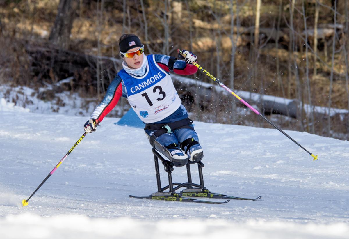 a female Para Nordic skier races towards the finish line
