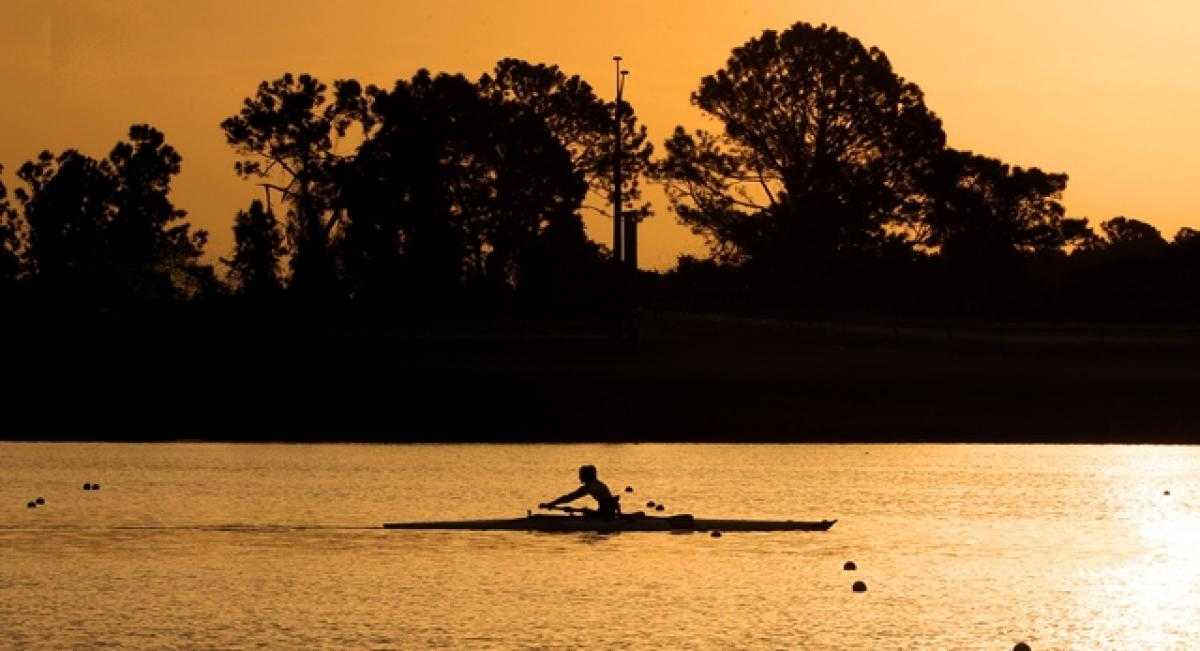 Sunset photo of rower in a boat on the water