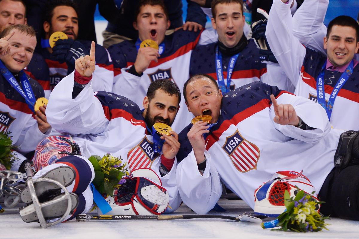a group of male para ice hockey players lie on the ice and bite their medals in celebration