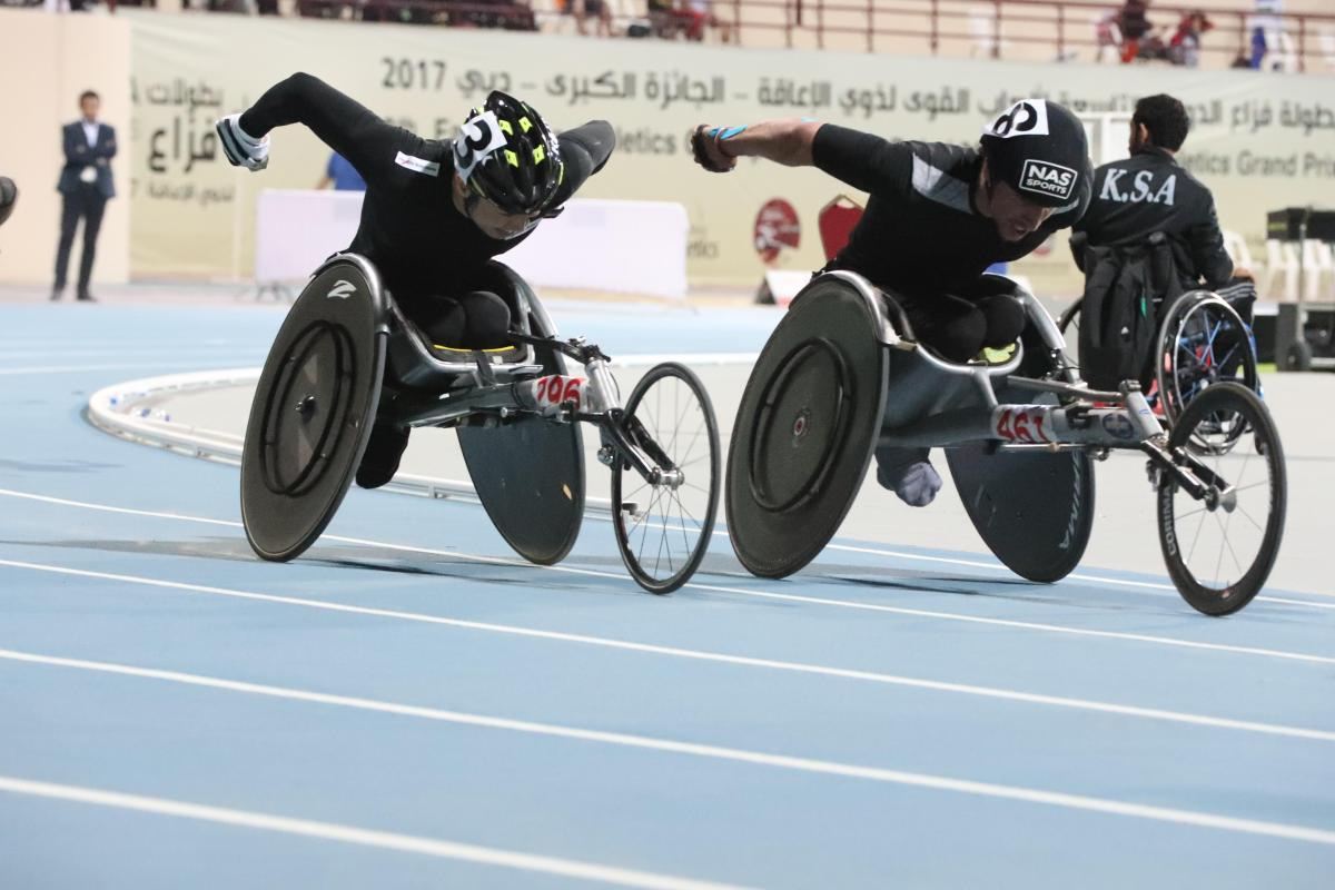 two male wheelchair racers come round the final bend
