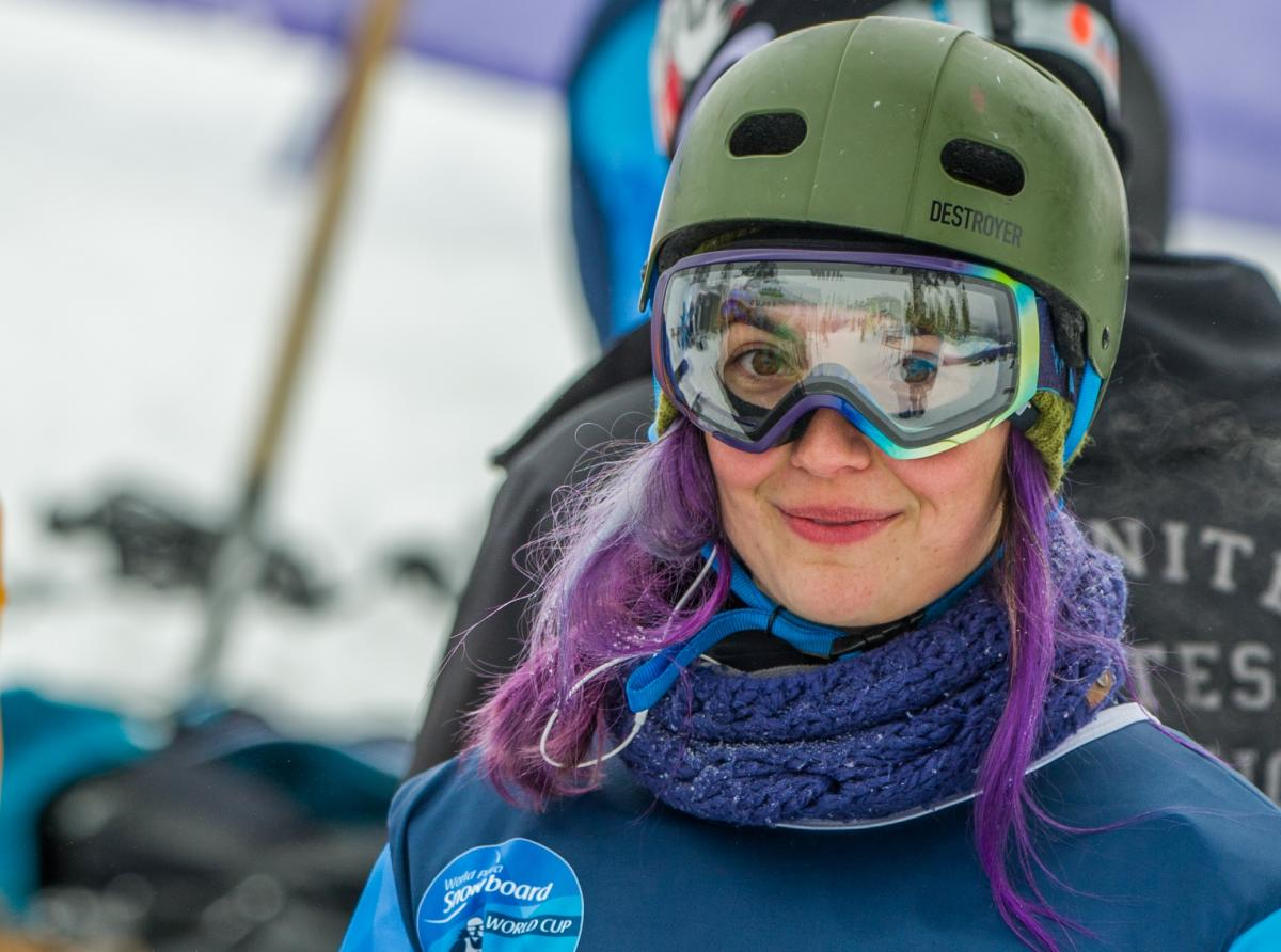 a female Para snowboarder smiles