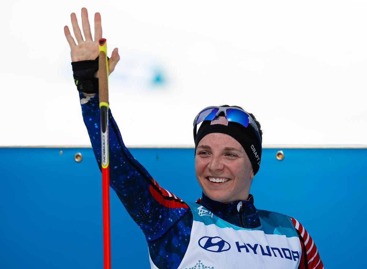 a female Nordic skier smiles and waves