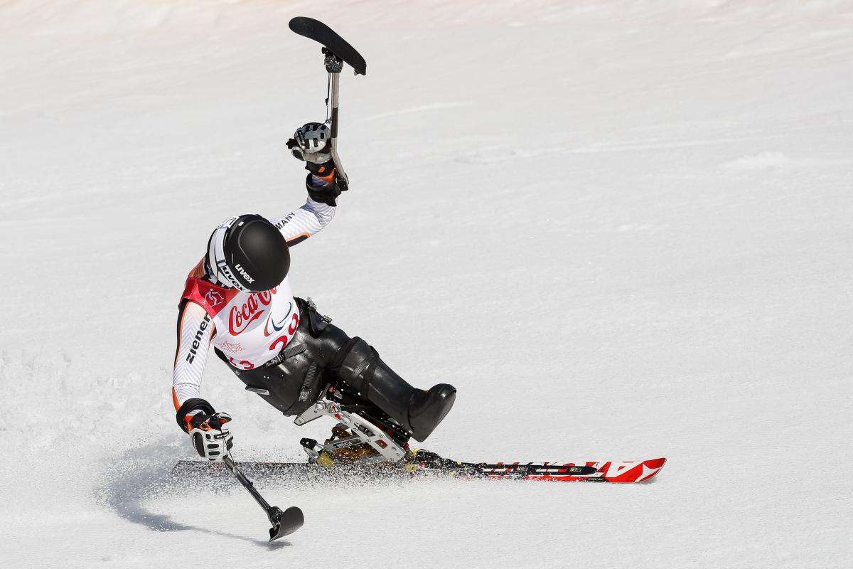a female sit skier celebrates with her ski in the air