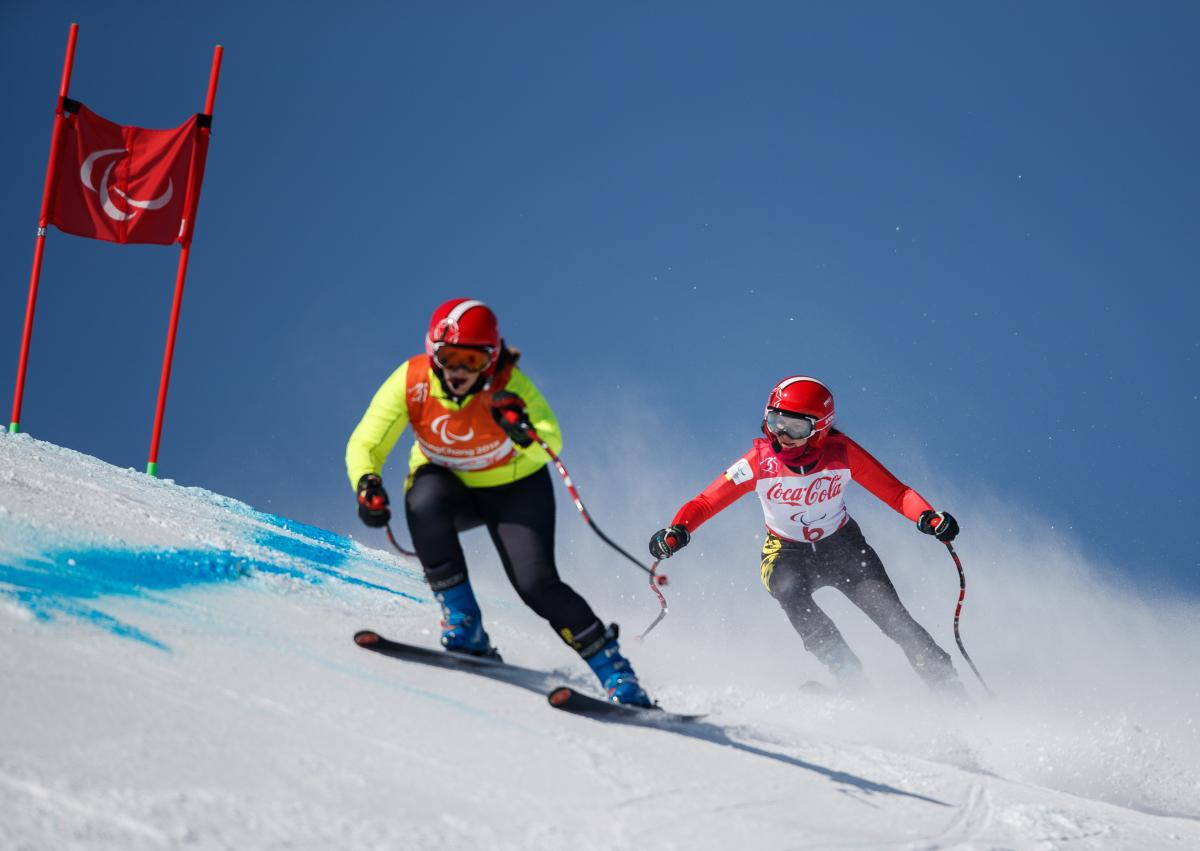 a female vision impaired skier and her guide take on a gate