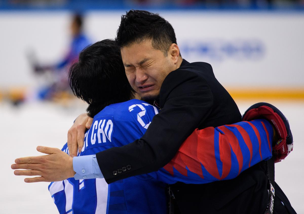 two men embrace and cry on an ice rink
