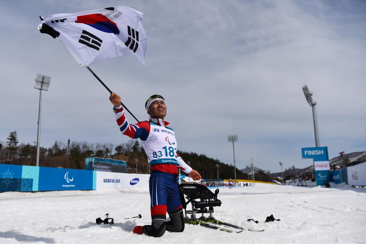 a male Para Nordic skier celebrates with the South Korean flag