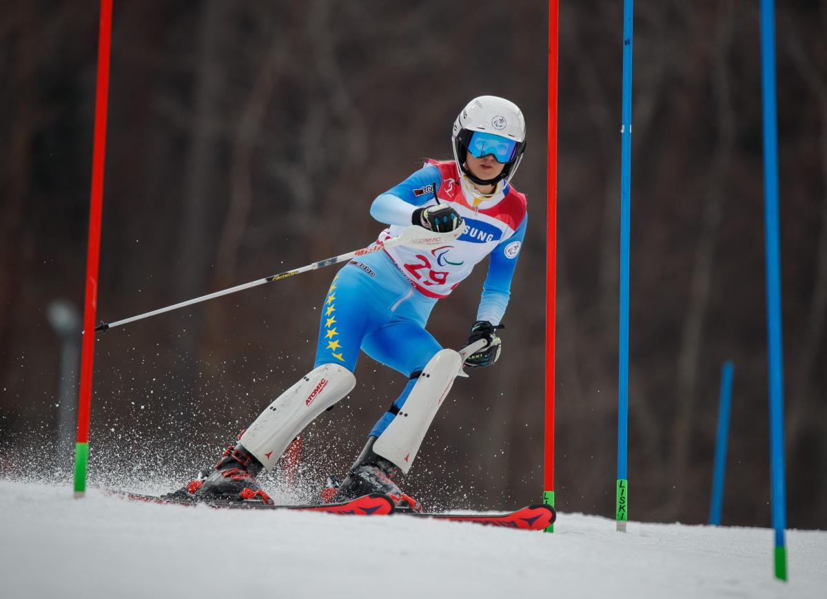 a female standing skier goes through a gate