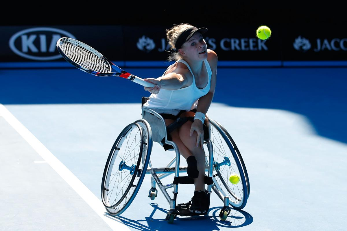 a female wheelchair tennis player makes a shot