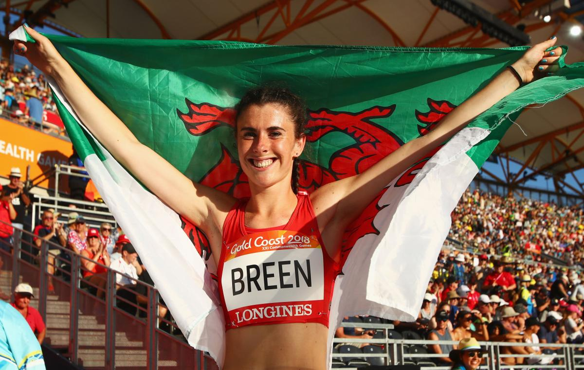 a female Para athlete holding up the Welsh flag
