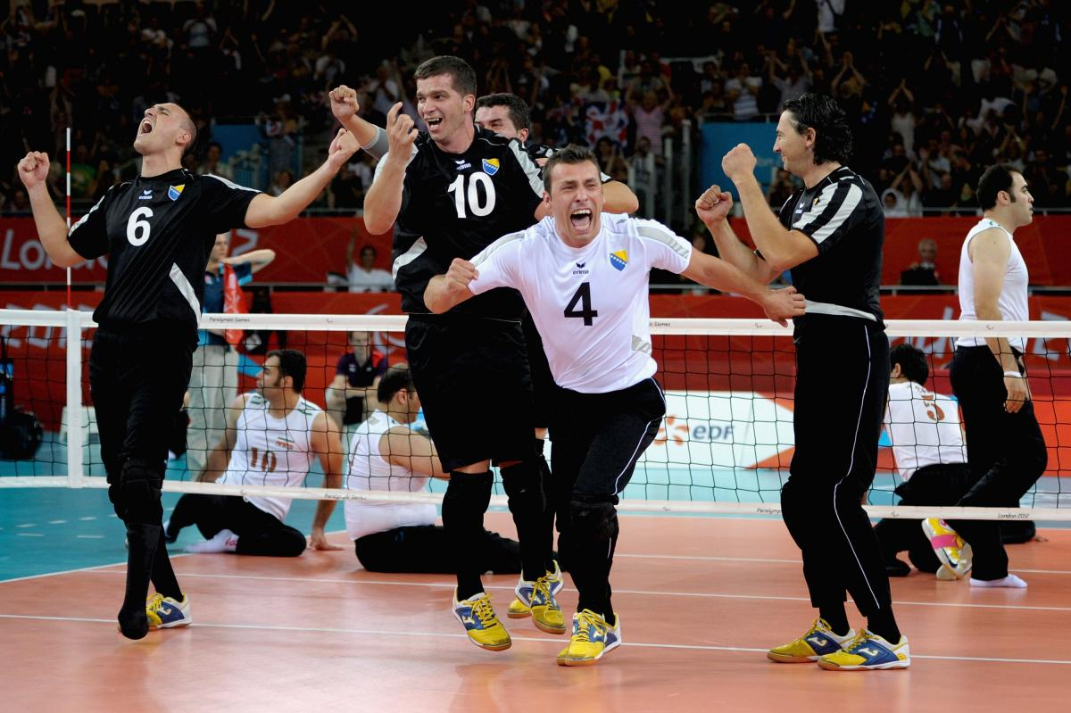 a group of male sitting volleyballers celebrate on the court