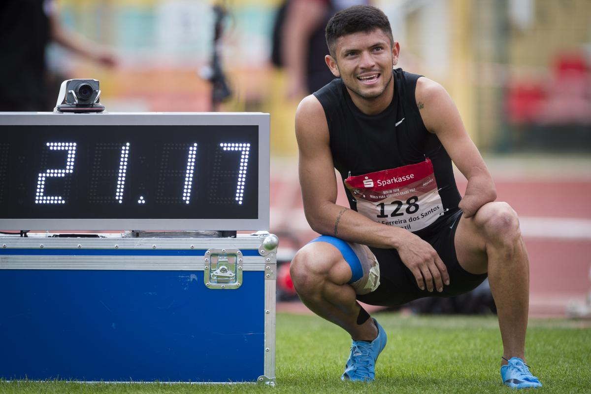 a male Para sprinter stands next to a race clock