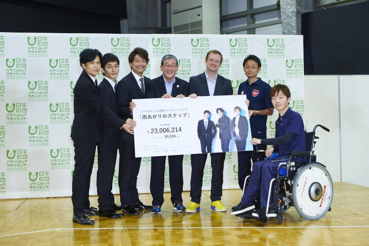 Six men standing and one in a wheelchair holding a cheque