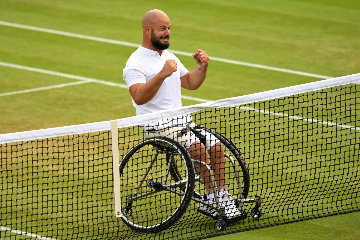 male wheelchair tennis player Stefan Olsson raises his fists in celebration at the net