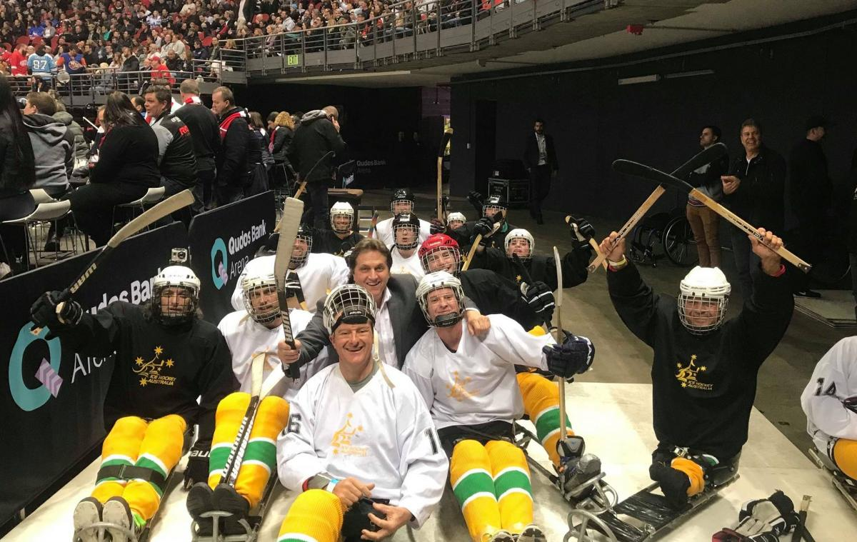 Fifteen people on sledges with Para ice hockey gear posing for a picture