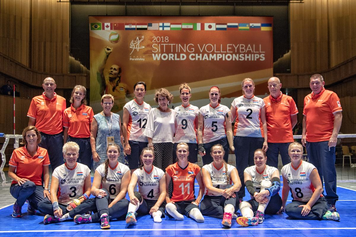 Princess Margriet and a group of female sitting volleyball players grouped together on a court