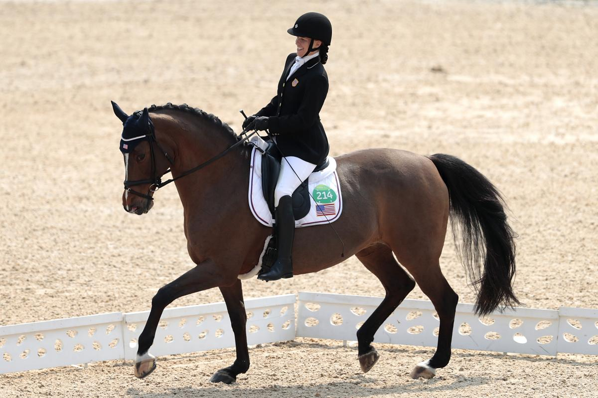 female Para equestrian rider Rebecca Hart competes on a horse in a dressage arena