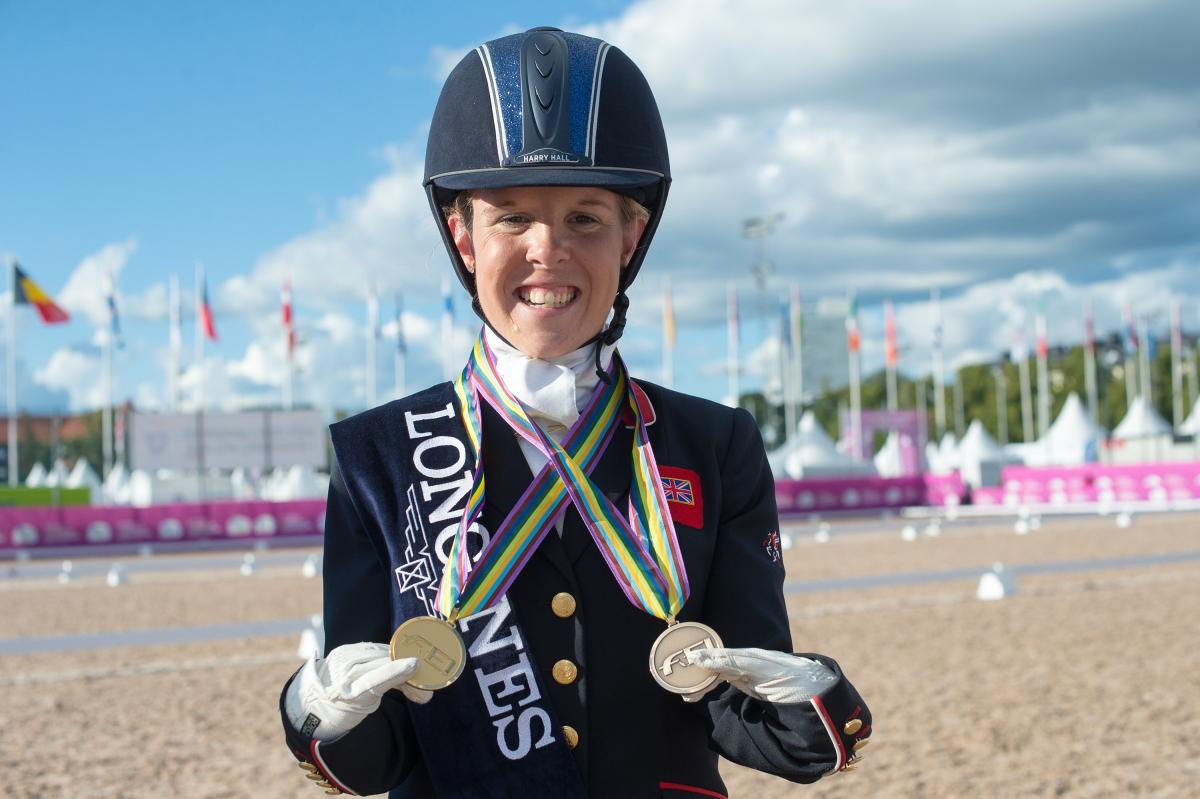 female Para equestrian rider Erin Orford smiles and holds up two gold medals around her neck