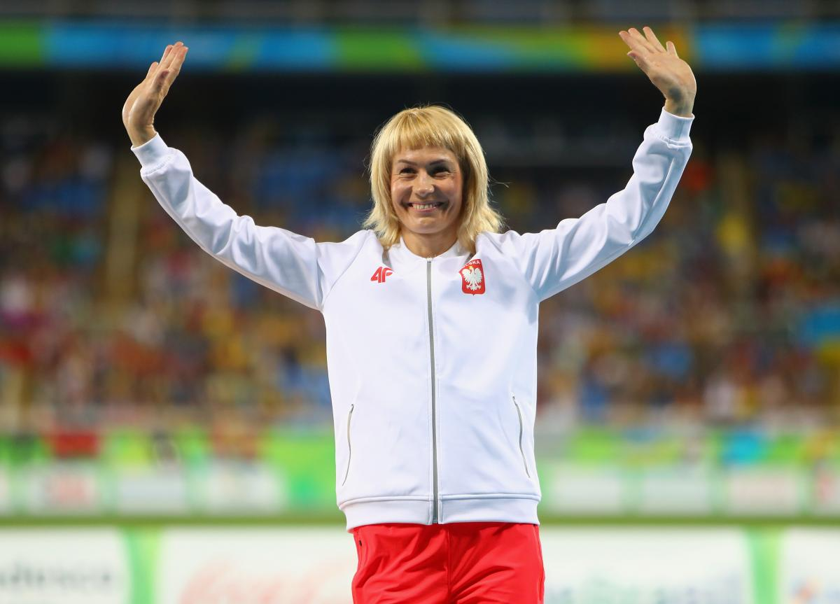 female Para sprinter Barbara Niewiedzial raises her arms on the podium