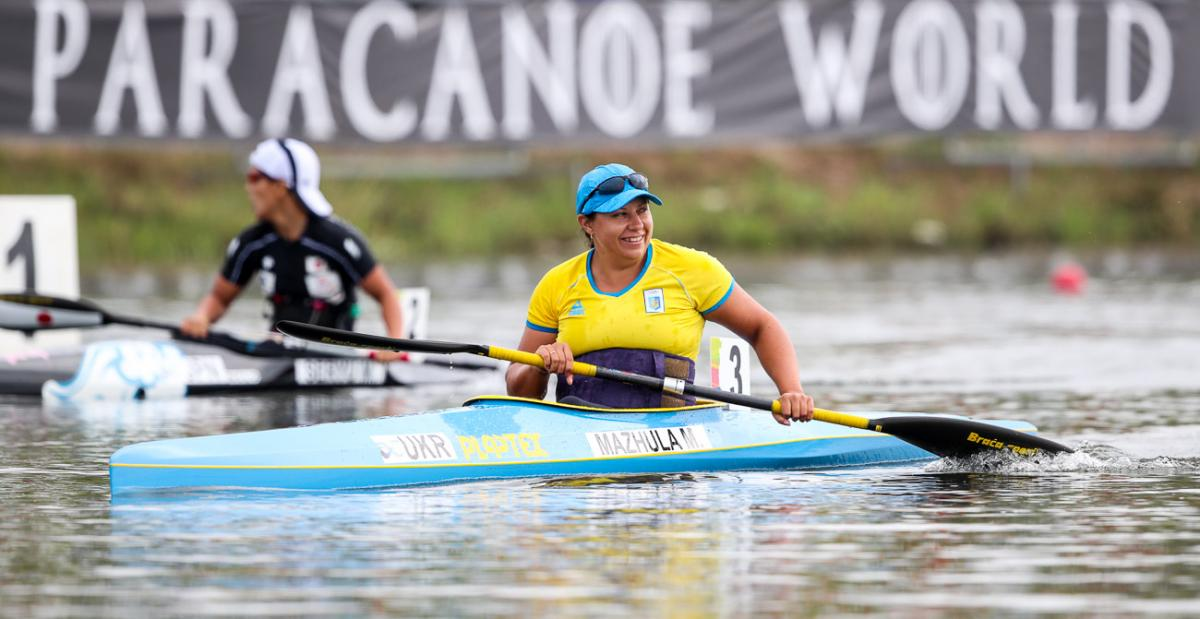 female Para canoeist Maryna Mazhula smiles in her boat after winning the race