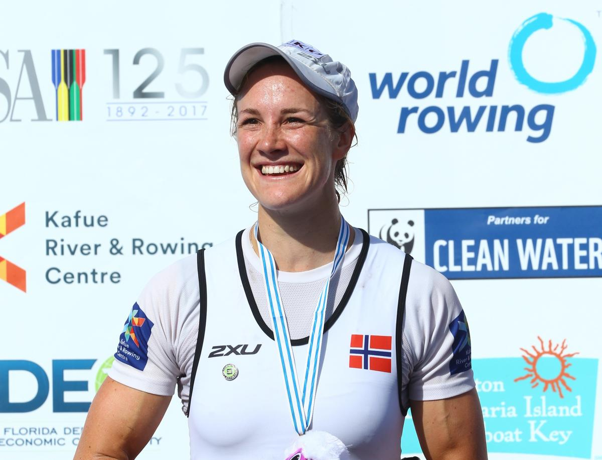 female Para rower Birgit Skarstein smiling with her medal on the podium