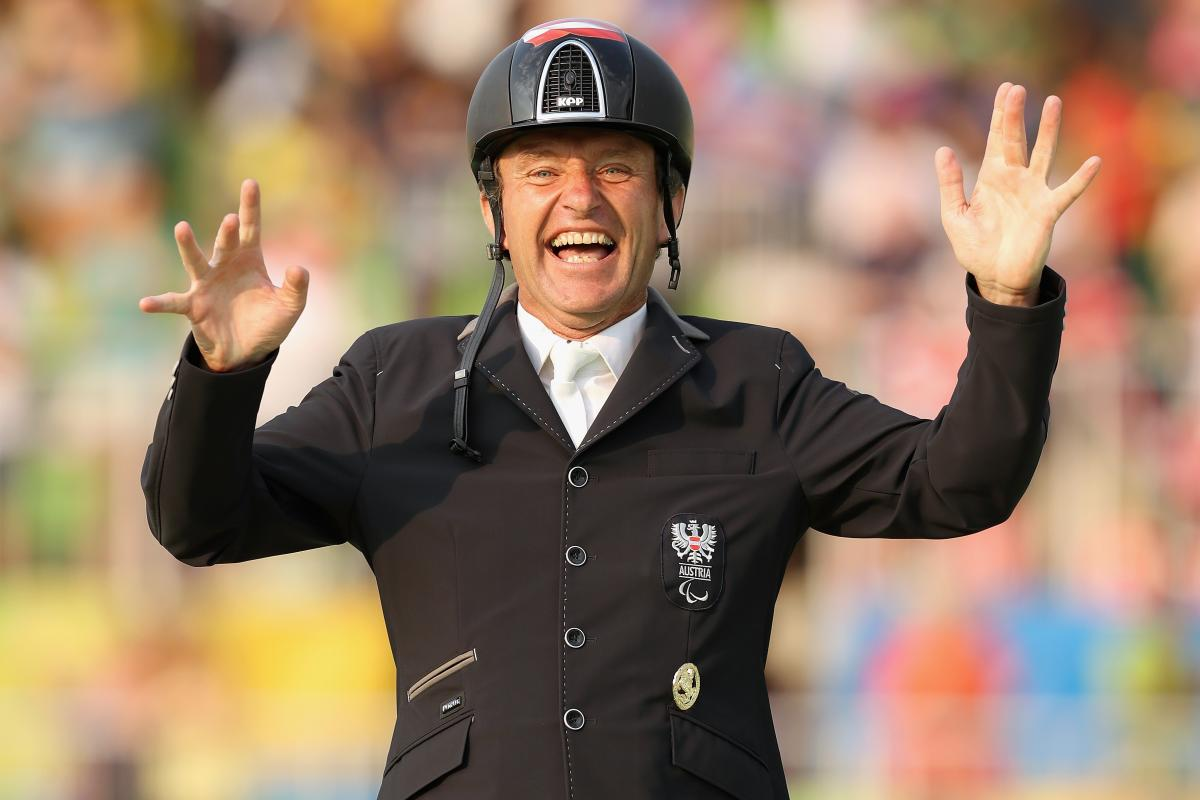 male Para equestrian rider Pepe Puch smiles and raises his hands in celebration