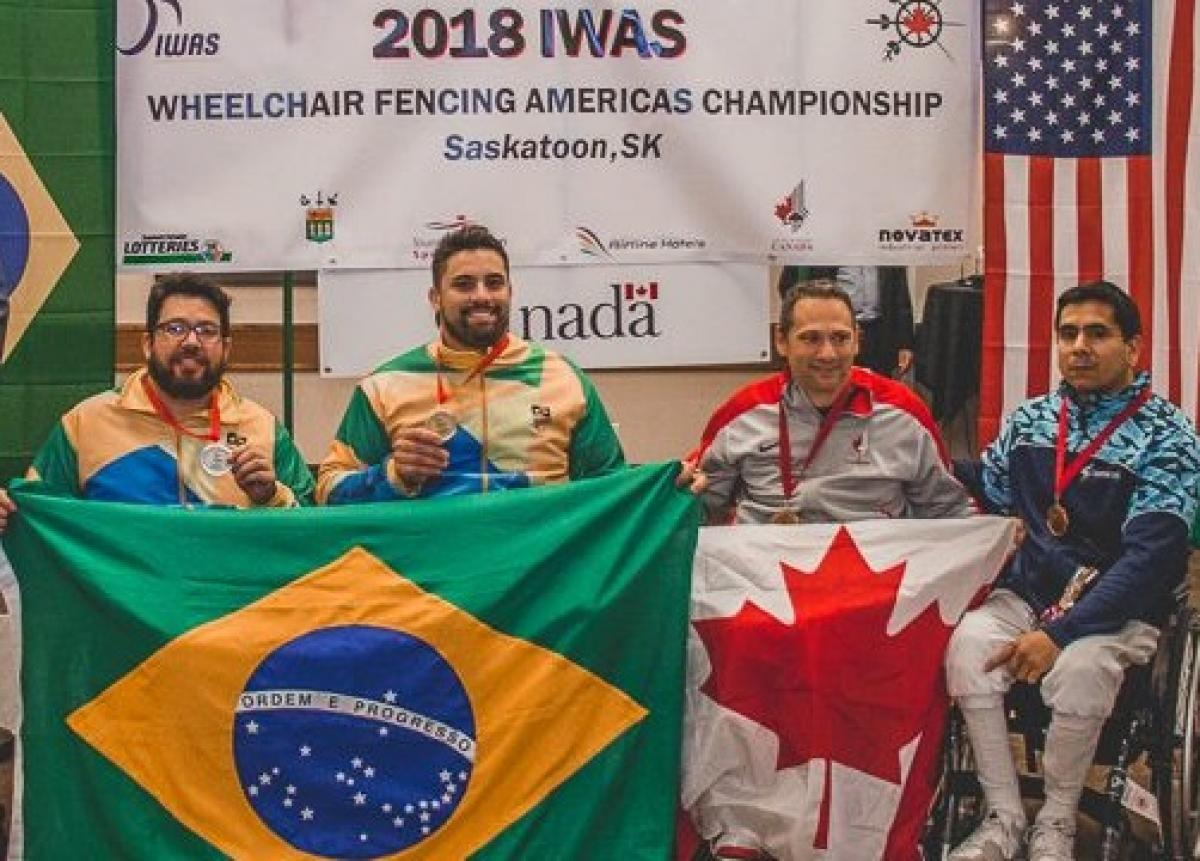 four male wheelchair fencers on the podium including Jovane Guissone holding a Brazilian flag