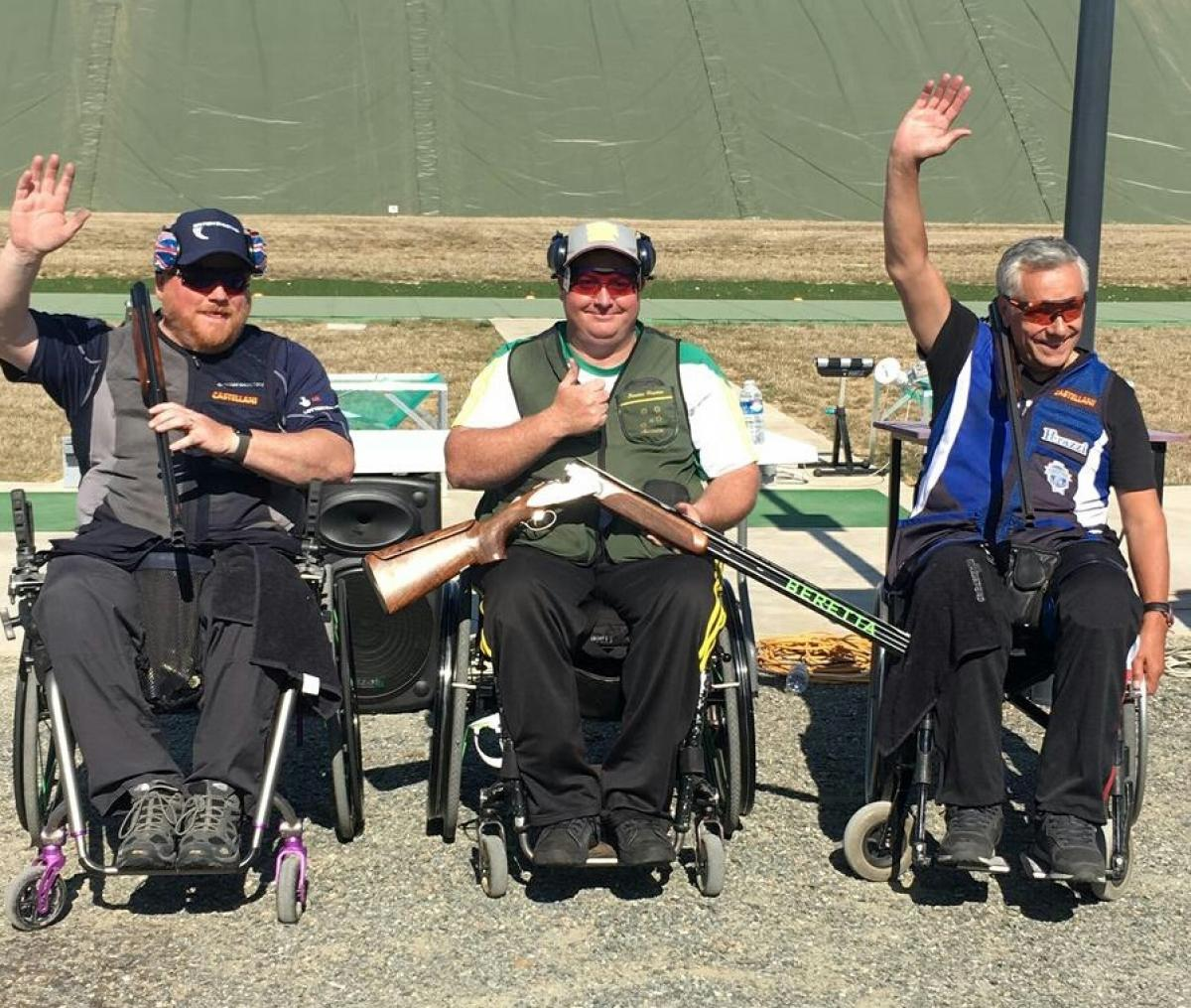 three male Para shooters in wheelchairs with Scottie Brydon in the middle waving to the crowd