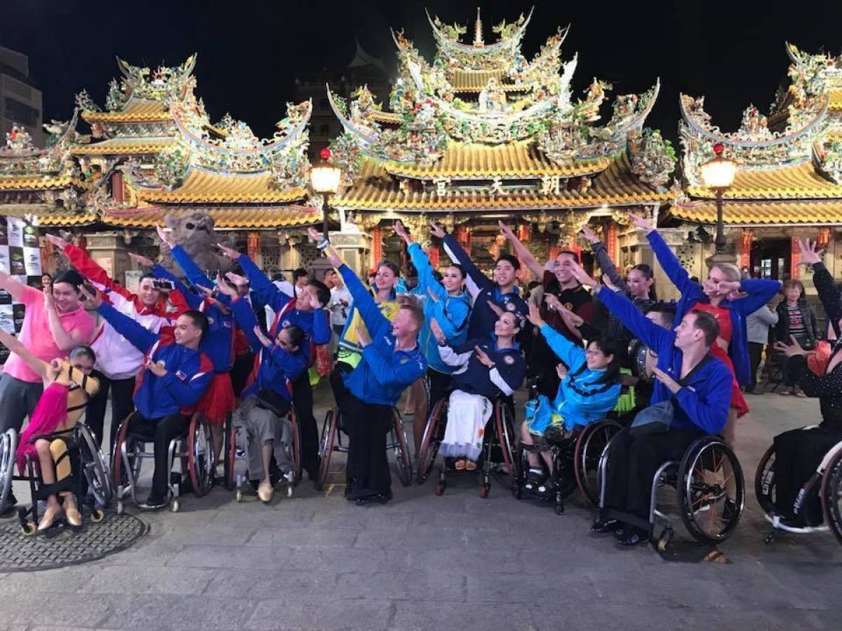 a group of Para dancers raising their arms in front of three golden Chinese temples