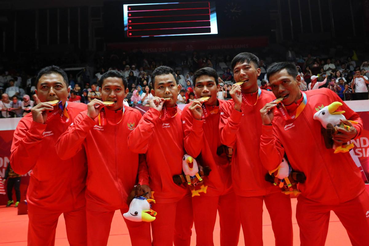 a group of Indonesian male Para badminton players biting their gold medals