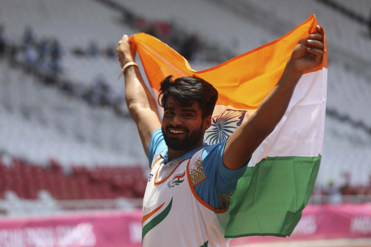 male Para athlete Sandeep Sandeep smiling and holding up an India flag