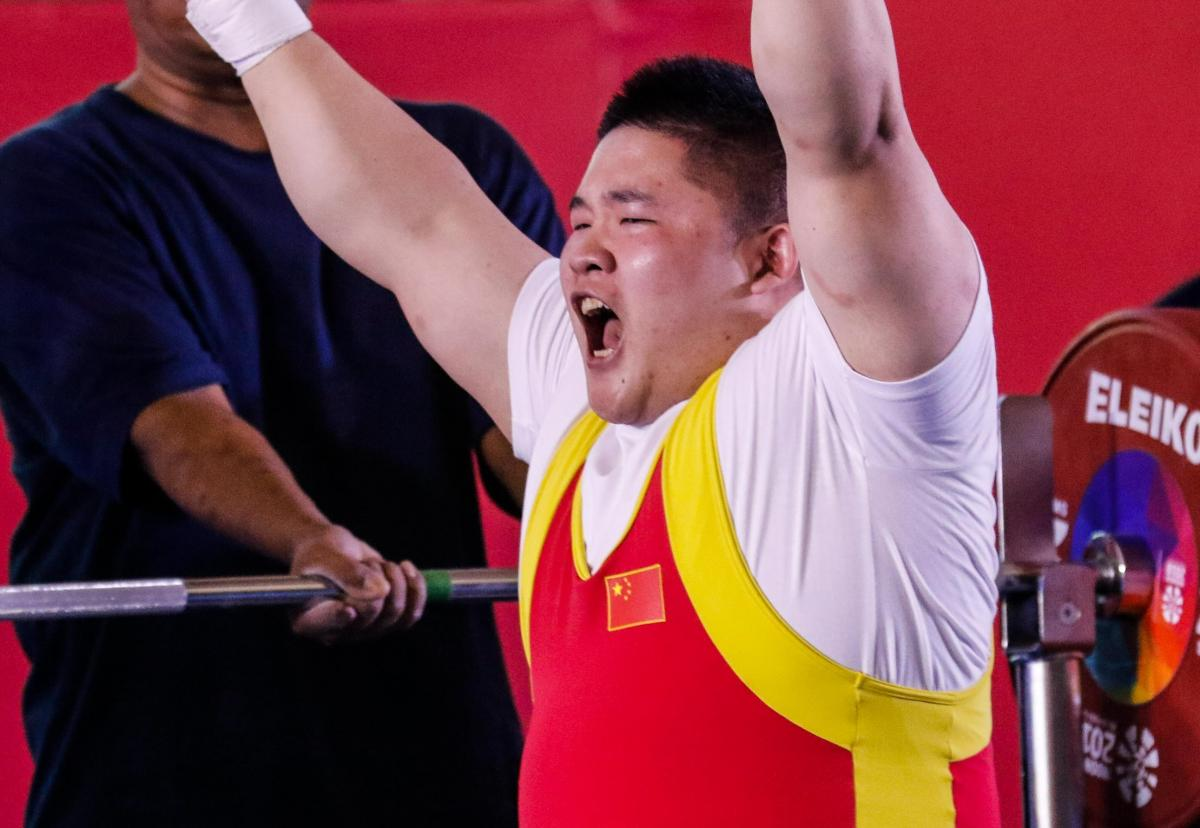 male powerlifter Jixiong Ye raises his arms in celebration