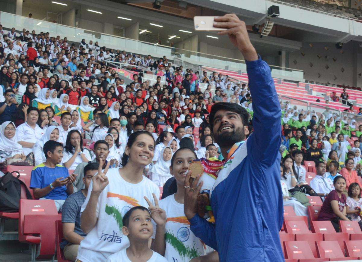 Man with a medal taking pictures with fans on the stands in a stadium