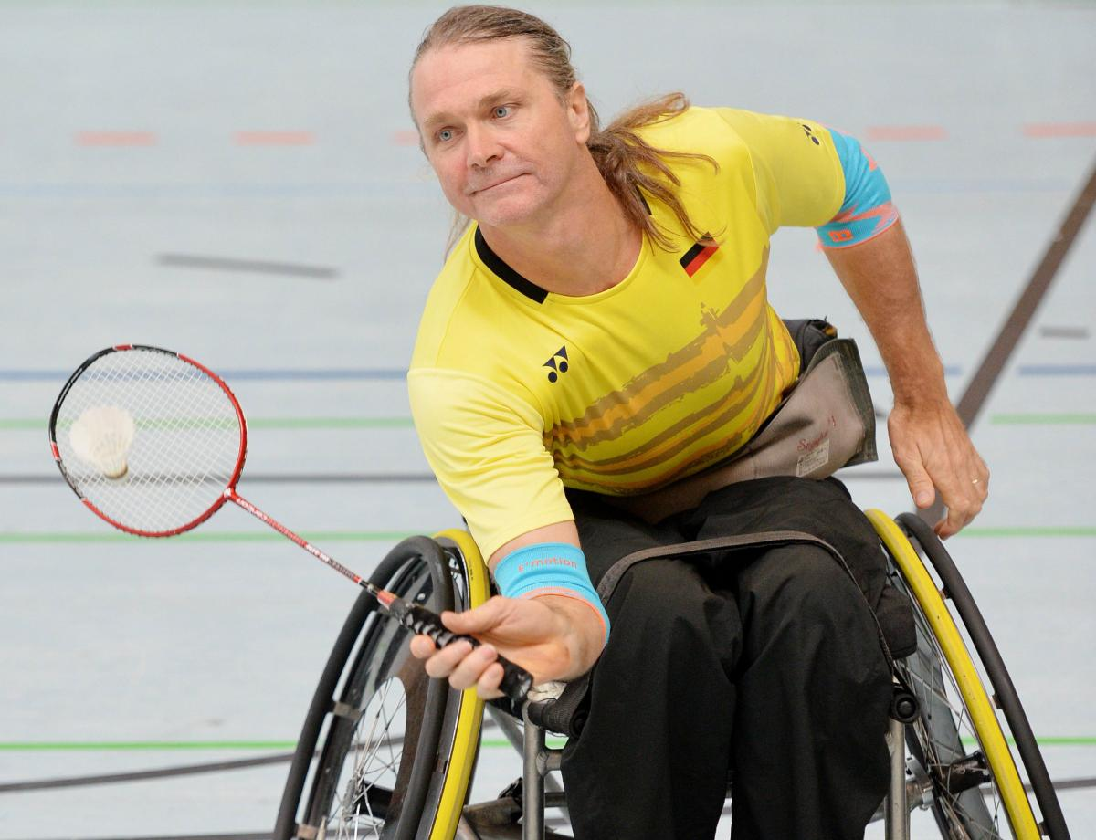 male Para badminton player Thomas Wandschneider reaches down to hit a forehand
