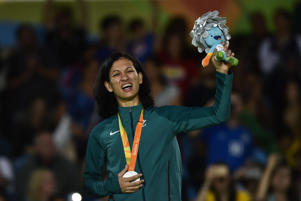 female judoka Lucia Araujo smiles on the podium holding up a mascot