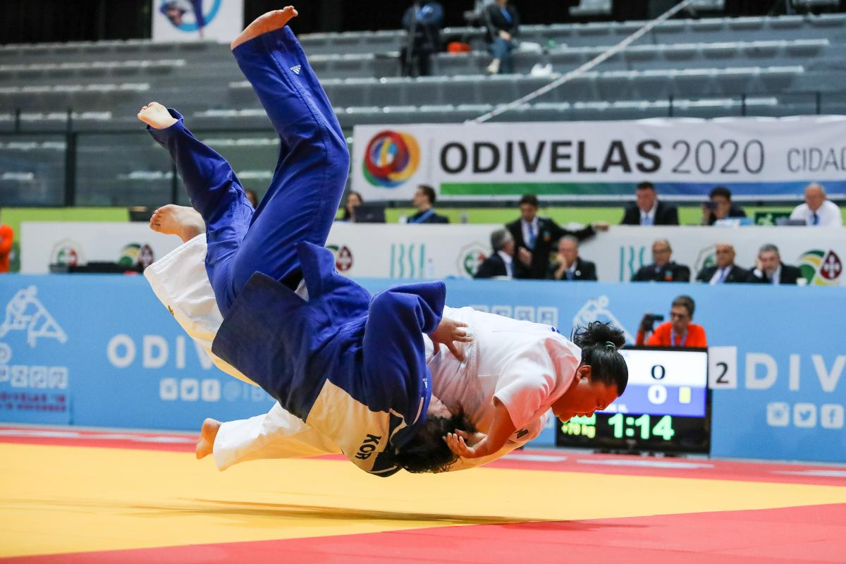 Judokas holding each other while falling onto the tatami
