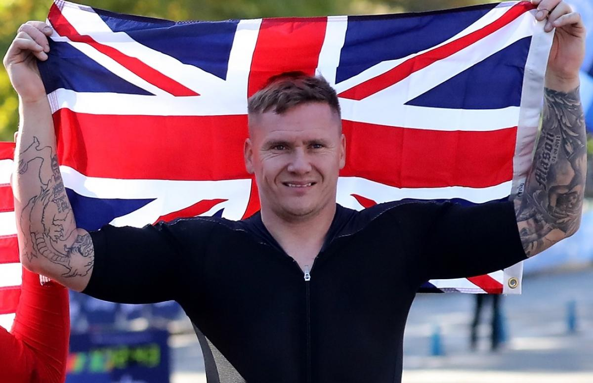 male marathon wheelchair racer David Weir holding up the British flag and smiling