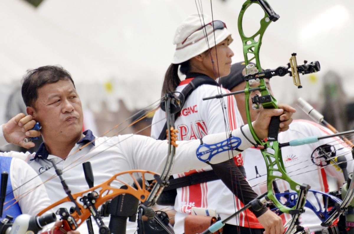 male Para archer Ouk-Soo Lee draws back his bow and prepares to shoot