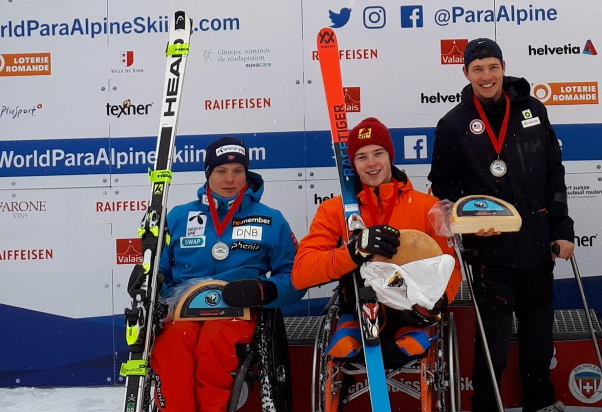 three Para alpine skiers holding up wheels of cheese on the podium