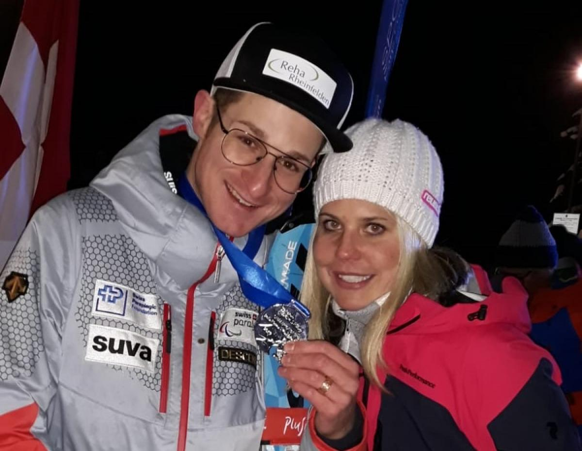 male Para alpine skier Thomas Pfyl hugs his wife Evelyn while both smile