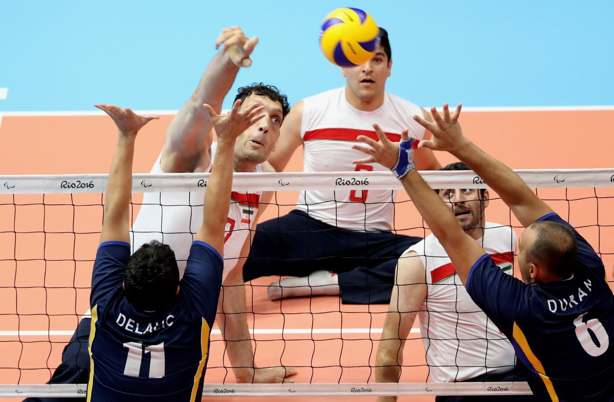 a group of male sitting volleyball players on court during a match