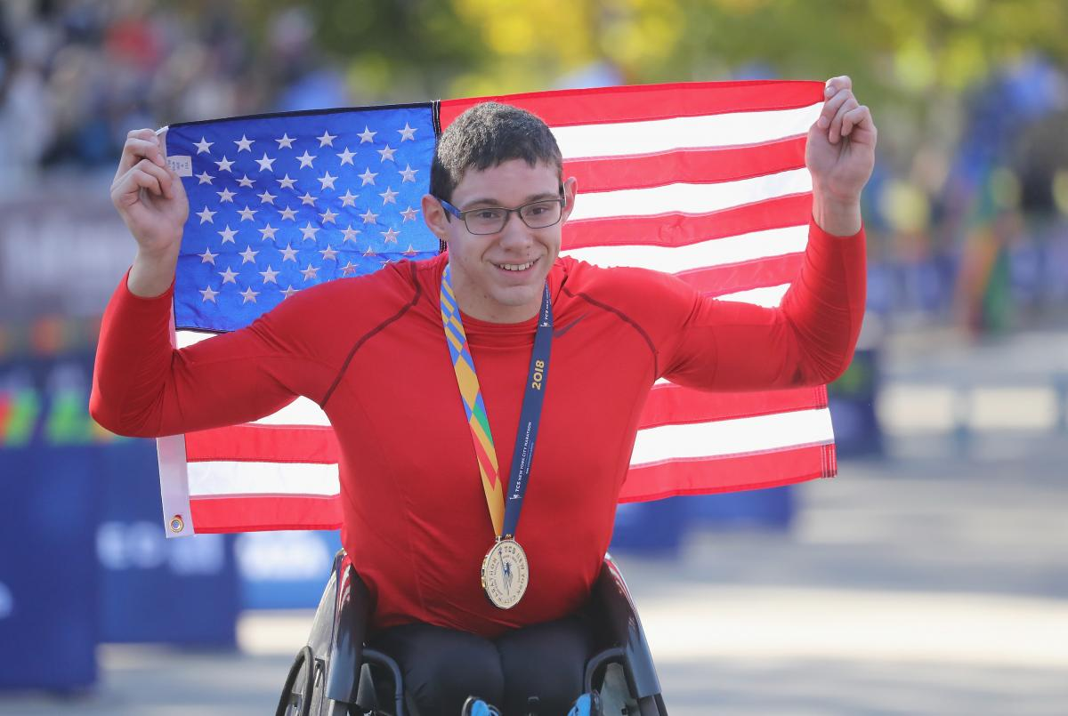 male wheelchair racer Daniel Romanchuk holding up a USA flag