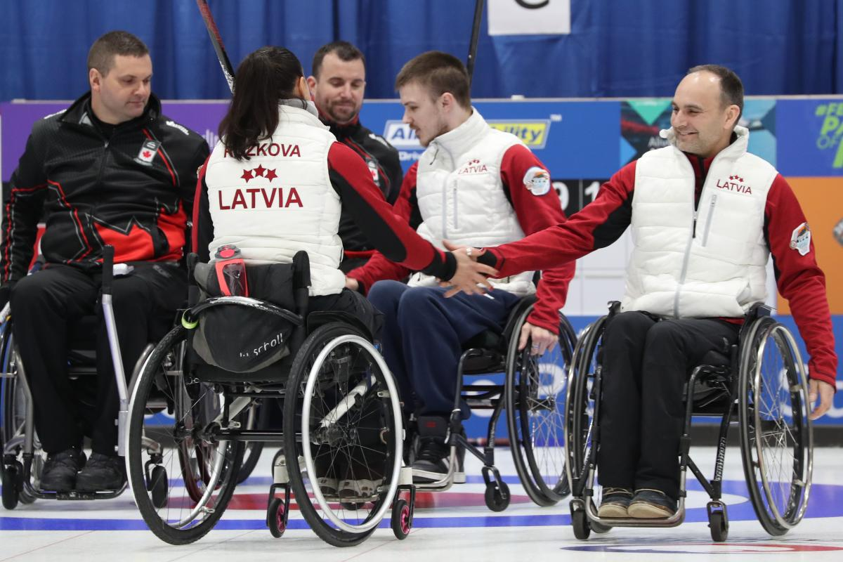wheelchair curlers from Latvia high-five after beating Canada on the ice