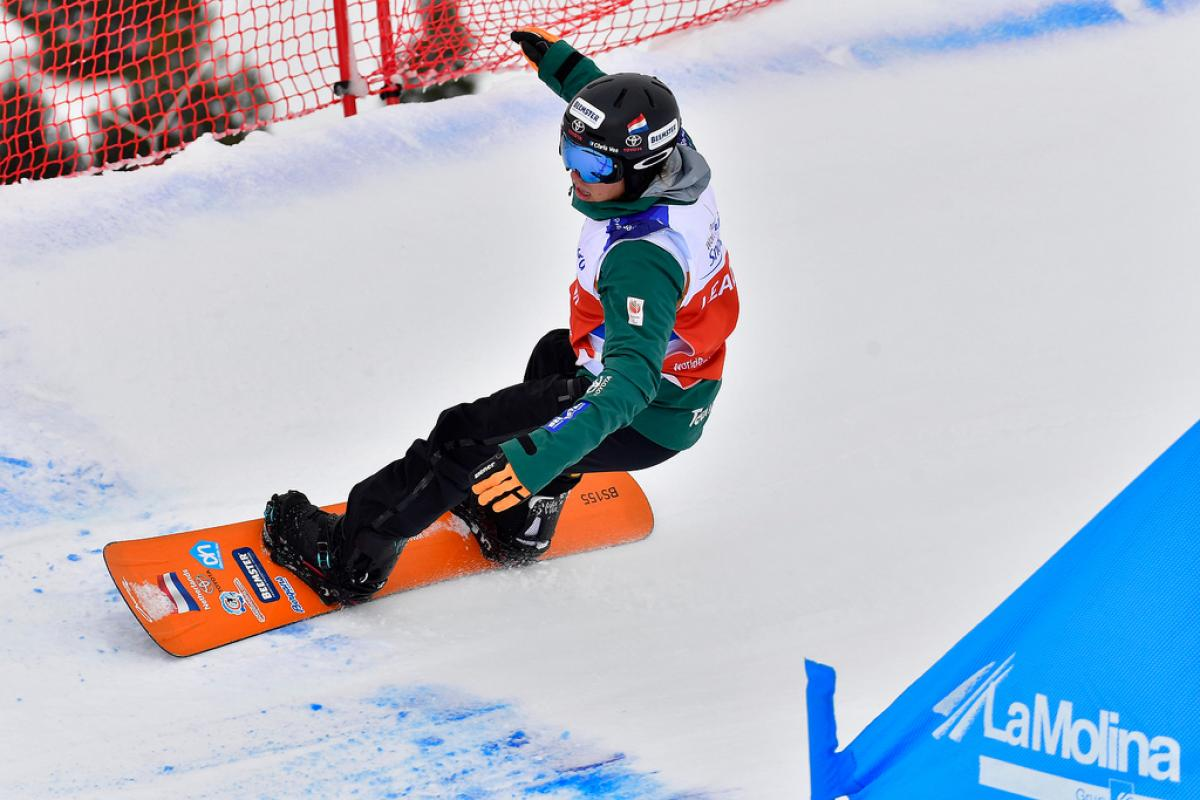male Para snowboarder Chris Vos goes round a banked slalom bend