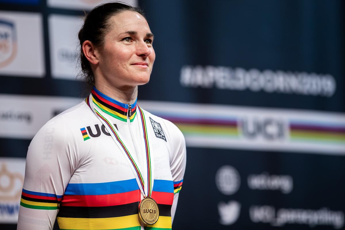 female Para cyclist Sarah Storey stands on the podium with a gold medal around her neck