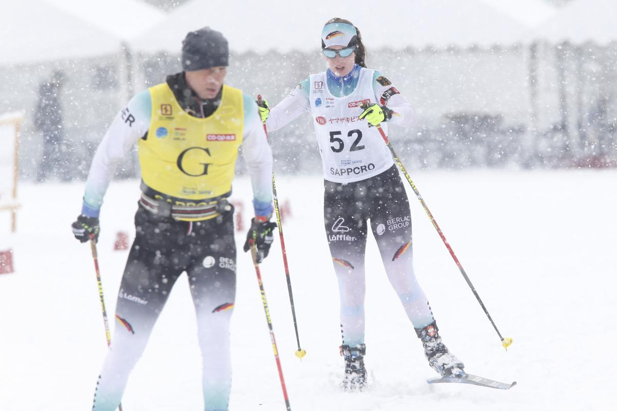 female Para Nordic skier Clara Klug skis towards the finish line behind her guide